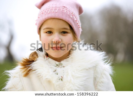 Close up portrait of a young and attractive child girl looking at the camera while standing in a  green park wrapped up during a cold winter day, wearing a woolly hat and being thoughtful. - stock photo