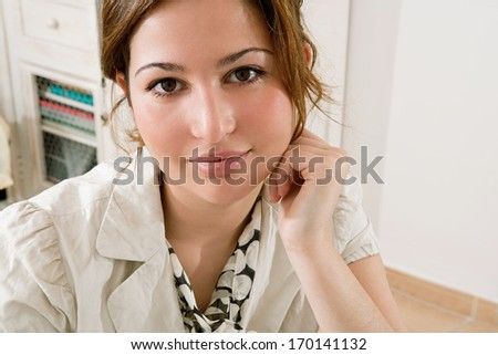 Close up portrait of a young and attractive professional business woman sitting and relaxing in her office work place, smiling a the camera while leaning on her hand wearing an elegant suit. - stock photo