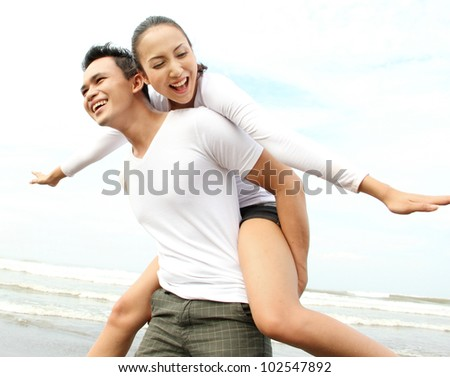 Close up portrait of a young asian man giving piggyback to woman on the beach. - stock photo