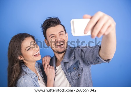 Close-up portrait of a young attractive couple are making a selfie picture isolated on blue background. - stock photo