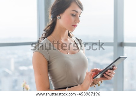 Close-up portrait of a young attractive freelancer using tablet for telework, typing and reading new messages on-line - stock photo