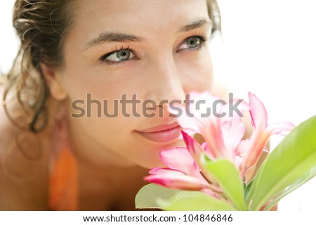 Close up portrait of a young attractive girl smelling a tropical pink flower in a white background.