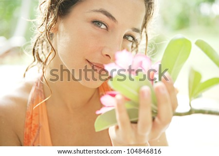 Close up portrait of a young attractive girl smelling a tropical pink flower in an exotic garden.