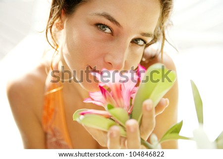 Close up portrait of a young attractive girl smelling a tropical pink flower in an exotic garden. - stock photo