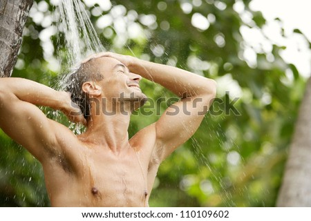 Close up portrait of a young attractive man having a shower in a tropical garden with palm trees while on vacations, smiling.