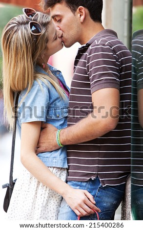Close up portrait of a young attractive romantic couple passionately kissing while shopping in a destination city while on holiday break, outdoors. Travel and lifestyle young people. - stock photo
