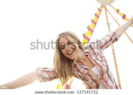 Close up portrait of a young attractive teenage girl in a colorful attractions park arcade, playing and being energetic with her arms outstretched up in the air. - stock photo