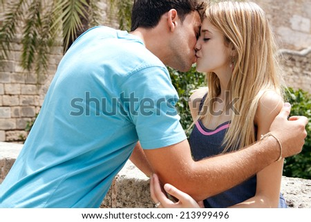 Close up portrait of a young attractive tourist couple being close and in love, kissing and hugging with passion and romance while on holiday, visiting a touristic destination city, outdoors. - stock photo