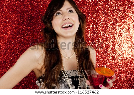 Close up portrait of a young attractive woman holding a cocktail glass while laughing against a red glitter background in a christmas party.