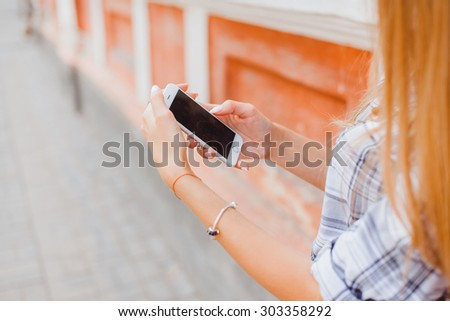 Close up portrait of a young attractive woman holding a smartphone digital camera with her hands and taking a selfie self portrait of herself winking at he camera. Travel and technology outdoors. - stock photo