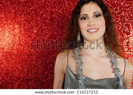 Close up portrait of a young attractive woman wearing christmas tinsel decorations as a necklace smiling against a red glitter background.