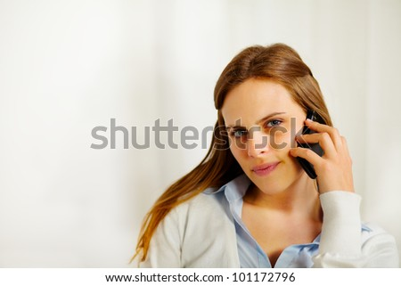 Close up portrait of a young beautiful businesswoman talking on the mobile phone - stock photo