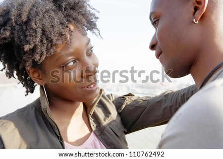 Close up portrait of a young black tourist couple visiting London city, facing each other and smiling.