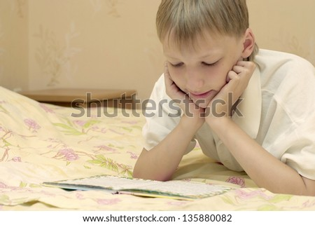close-up portrait of a young boy reading a book - stock photo