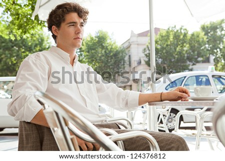 Close up portrait of a young businessman having a coffee while sitting outdoors at a coffee shop terrace table in the shade on a sunny day.