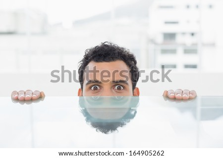 Close-up portrait of a young businessman peeking behind the desk at bright office - stock photo