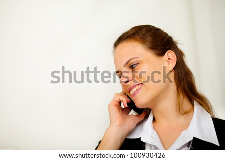 Close up portrait of a young businesswoman on cell phone and smiling - stock photo