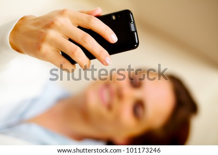 Close up portrait of a young caucasian woman lying on sofa and using a cell phone - stock photo
