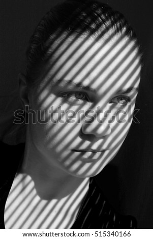 Close-up portrait of a young Caucasian woman with shadows shaped like stripes on her face, looking away from camera, in black and white