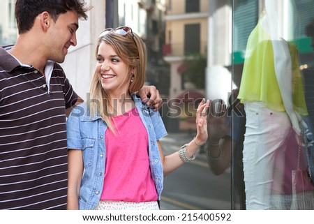 Close up portrait of a young couple on holiday visiting shopping streets and enjoying a vacation city break, outdoors. Travel, consumer and lifestyle. - stock photo