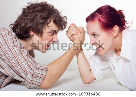 Close-up portrait of a young couple that fights on his hands on a light background