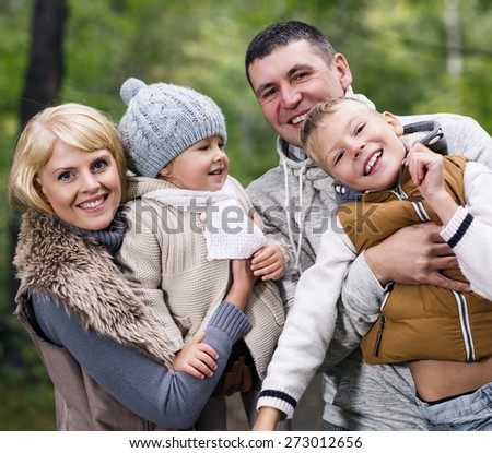 Close up portrait of a young family in the autumn park