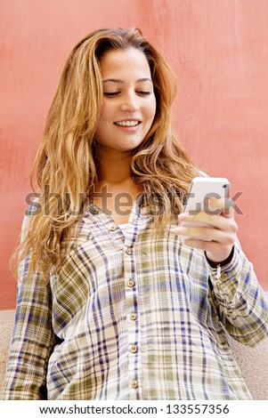 Close up portrait of a young fashionable woman holding a smartphone while leaning on a bright orange color texture wall in the city, smiling. - stock photo