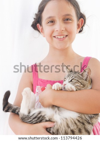 Close up portrait of a young girl holding a kitten in her arms and smiling at the camera.