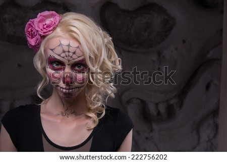 Close-up portrait of a young girl in black dress with Calaveras makeup and a red flower in her blonde hair looking straight at the camera in ancient temple interior