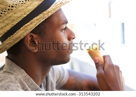 Close up portrait of a young guy with hat eating ice cream - stock photo