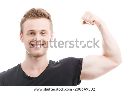 Close up portrait of a young handsome man wearing black t-shirt and blue shorts standing smiling and showing his muscled biceps during training, isolated on white background - stock photo