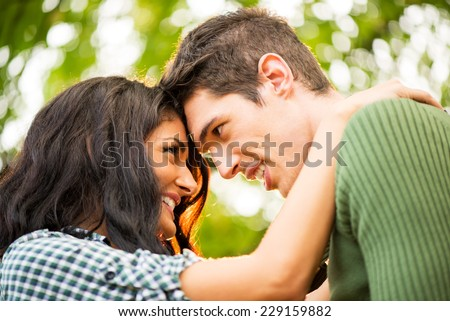 Close-up portrait of a young heterosexual couple in love to watch each other lovingly leaning their heads on each other. - stock photo