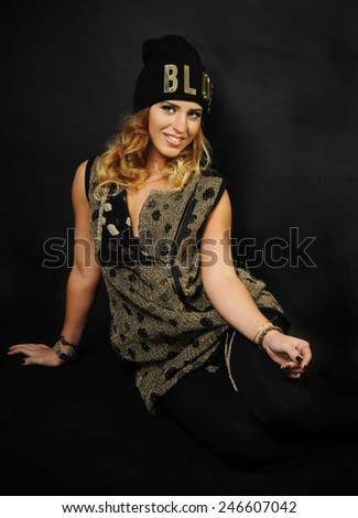close up portrait of a Young latin girl wearing black and Golden vest and black hat with a word blog written on it seating on a black background - stock photo