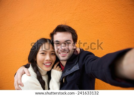 Close up portrait of a young man and woman smiling while taking selfie - stock photo