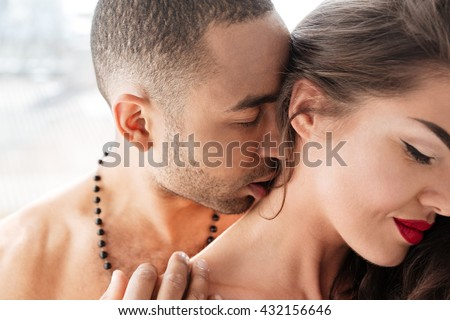 Close-up portrait of a young man kissing woman's neck indoors