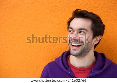 Close up portrait of a young man smiling face looking at copy space - stock photo