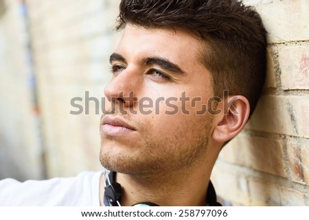 Close-up portrait of a young man with blue eyes posing near a wall. Model of fashion in urban background wearing white t-shirt - stock photo