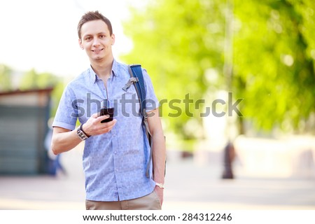 Close up portrait of a young man with phone and backpack - stock photo