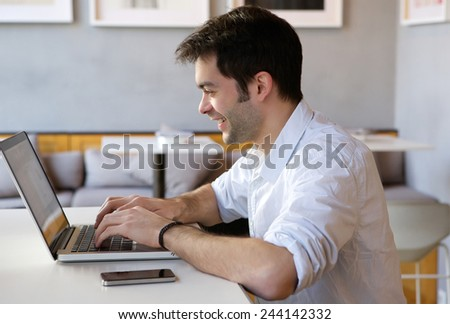 Close up portrait of a young man working on laptop indoors - stock photo
