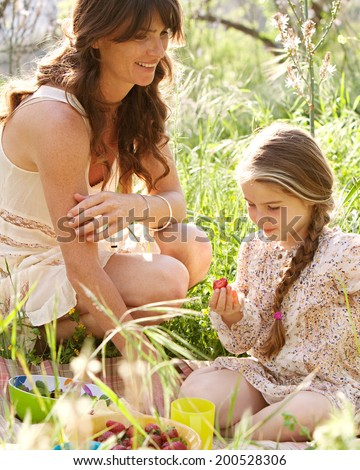 Close up portrait of a young mother and daughter relaxing together having a picnic in a green garden eating healthy food, smiling having fun. Family activities and healthy eating lifestyle, outdoors. - stock photo