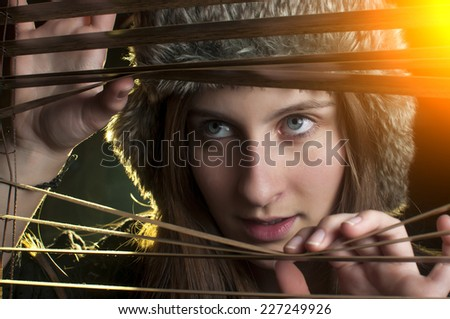 Close-up portrait of a young pretty girl peeking through blinds. Winter close up portrait - stock photo