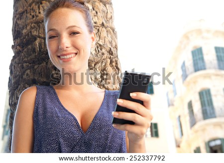 Close up portrait of a young professional tourist woman visiting a destination city, using a smartphone mobile phone to connect on line on holiday. Travel and technology lifestyle and networking. - stock photo