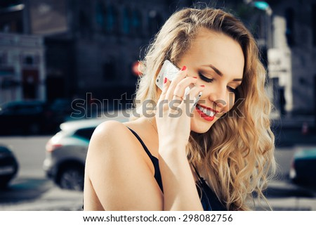 close-up portrait of a young sexy girl hipster beautiful blonde in glasses with red lips laughing and posing against the backdrop of the city - stock photo