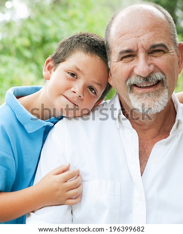 Close up portrait of a young son and his grandfather relaxing and hugging in a green garden during a sunny day, enjoying each others company and smiling joyfully. Outdoors active lifestyle. - stock photo