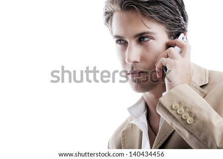Close-up portrait of a young sophisticated businessman talking on a mobile phone