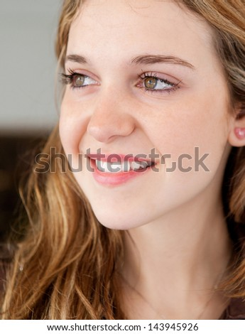 Close up portrait of a young stylish teenager woman leaning on a selective store shop window with reflections while on a shopping trip to the city mall, joyful and smiling. - stock photo