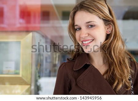 Close up portrait of a young stylish teenager woman leaning on a selective store shop window with reflections while on a shopping trip to the city mall, joyful and smiling at camera. - stock photo