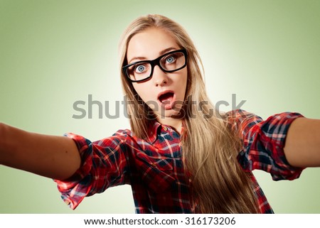 Close up portrait of a young surprised blonde girl holding a smartphone digital camera with her hands and taking a selfie self portrait of herself standing against blue background
