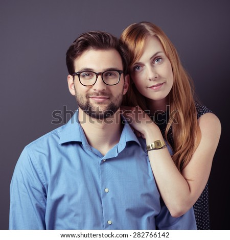 Close up Portrait of a Young Sweet Professional Couple Smiling at the Camera Against Gray Background.