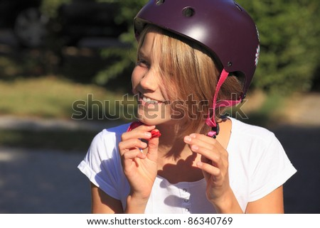 Close-up portrait of a young teenager girl buckle up her bicycle helmet